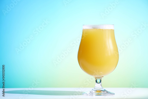 фотография A hazy New England India pale ale beer in a tulip shaped glass against a blue background