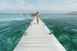 Young woman in bikini walking on wooden pier with beautiful tropical sea view. Vacation on tropical island.