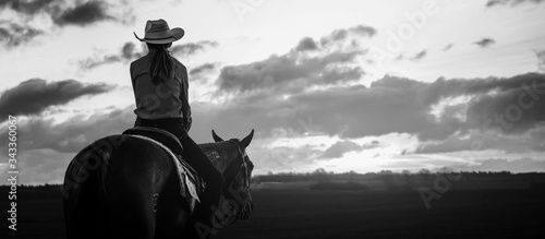 Fototapeta Girl ride on a horse in farm open field at afternoon dark sunset time.black and white  obraz