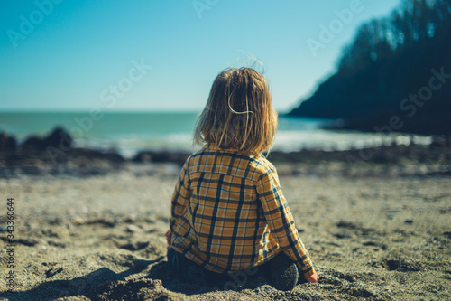 Little preschooler sitting on the beach in springtime Wallpaper Mural