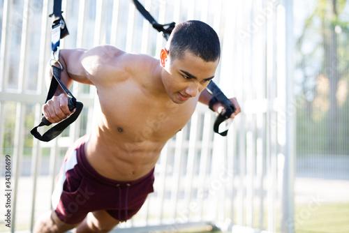 Cooler und muskulöser junger Mann trainiert im Freien mit einem Schlingentrainer Canvas Print