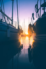 Silhouette Of Boats Sailing In Sea At Sunset