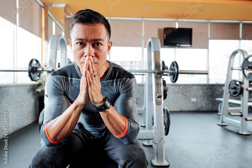 Valokuvatapetti Serious gym owner with pain in his eyes praying for ending of the pandemic and o
