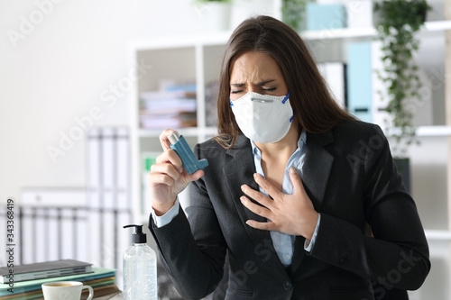 Photo Executive wearing mask with asthma holding inhaler