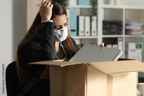 Fotografie, Obraz Fired executive with mask packing belongings at night