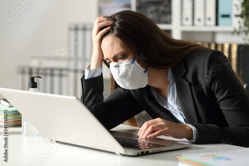 Fotomural Sad executive with mask reading bad news on laptop