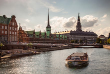 Ferry On River By Borsen Building And Christiansborg Palace Against Cloudy Sky