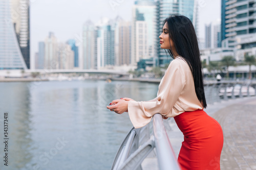 Photo Professional business woman in office attire on a boardwalk with skyscrappers ba
