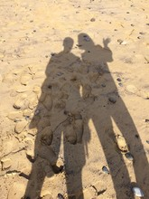 Footprints And Shadow Of People On Beach