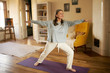 canvas print picture - Full length shot of happy energetic mature woman in casual clothes exercising at home because of social distancing, practicing yoga on mat, standing in warrior ii pose. Age, wellness and health
