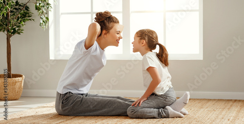 Stampa su Tela Fit mother and daughter training together at home.