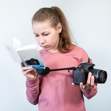 Preteen Girl Reading Service Manual Book For Her Dlsr Camera, Beginner Is Learning Photography, Grey Background