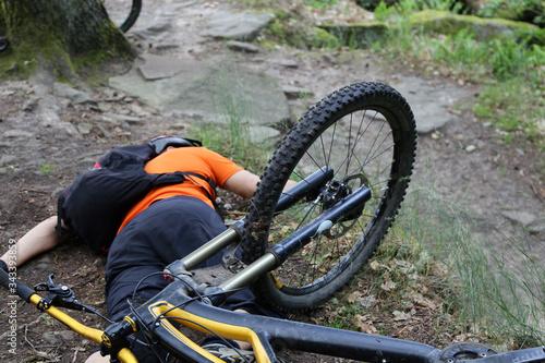 Photo Verunfallter Mountainbiker liegt verletzt auf dem Boden (Model released)