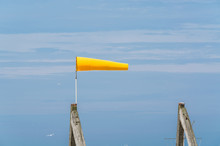 Side View Of Windsock Blowing In Wind Against Sky