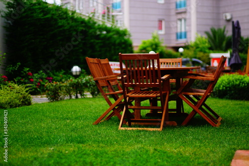 Fototapeta wooden garden table and chairs. Wooden dining table and wooden chairs on the grass. obraz