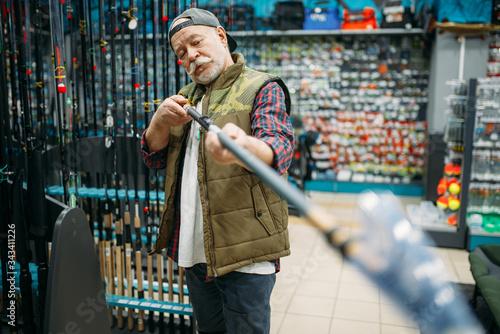 Photo Male angler choosing rod in fishing shop