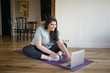 Online training, active lifestyle and vitality. Happy sporty girl with curvy body using laptop being strongly motivated by fitness instructor on video lesson, going to exercise on mat at home