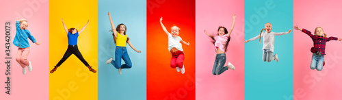 Vászonkép Emotional kids and teens jumping high, look happy, cheerful on multicolored background