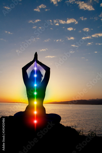 Photo Silhouette of woman sits in a lotus pose on beach sunset view, glowing seven all chakra