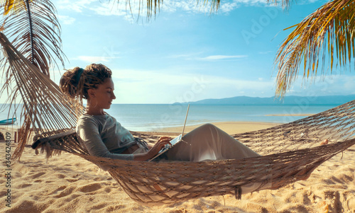 Photo Young woman working on laptop lying in hammock at sand beach of tropical island