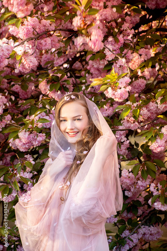 portrait of a beautiful teenager girl in delicate sakura flowers with a veil Canvas Print