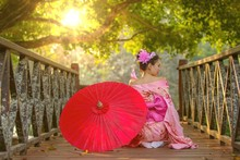 Asian Woman In Kimono. Japanese Girl Wearing A Kimono Holding A Red Umbrella. Beautiful Girl Wearing Japanese Traditional Clothing On The Wooden Bridge