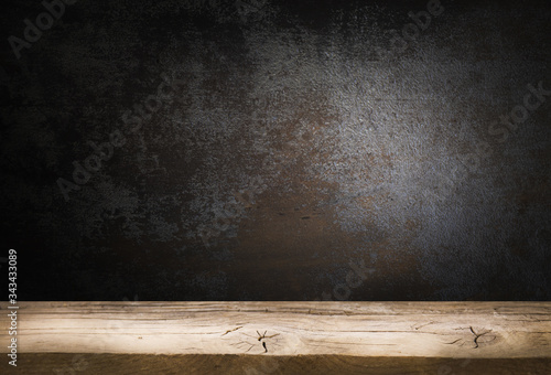 Old wooden table top with a dirty concrete block wall in a dark room background Wallpaper Mural