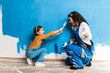 Leinwandbild Motiv Mother and daughter enjoying together while painting wall.