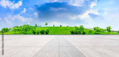 Empty square ground and green grass with tree under blue sky.