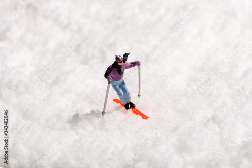 Lone miniature man skiing on fresh winter snow Billede på lærred