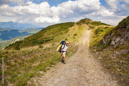 Fotomural Hiker with backpack going uphill