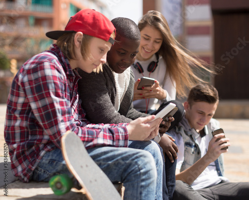 multinational teenagers play in smartphones in schoolyard Canvas Print