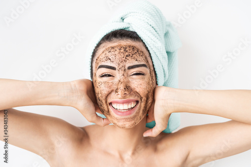 Young smiling woman applying coffee scrub mask on face - Happy girl having skin Wallpaper Mural