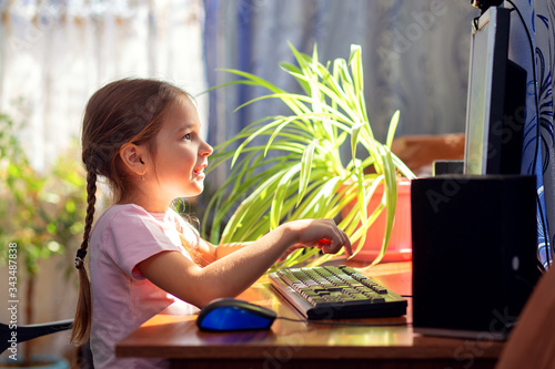 Fototapeta Girl schoolgirl is sitting at home at a computer desk and is engaged on a desktop computer