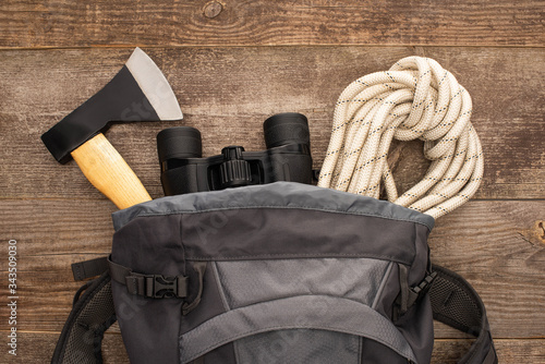 Obraz top view of backpack with axe, hiking rope and binoculars on wooden surface - fototapety do salonu
