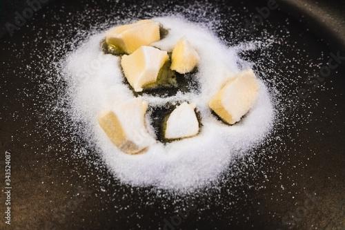 Photo Preparing an applesauce, on a frying pan melt butter and sugar to make caramel