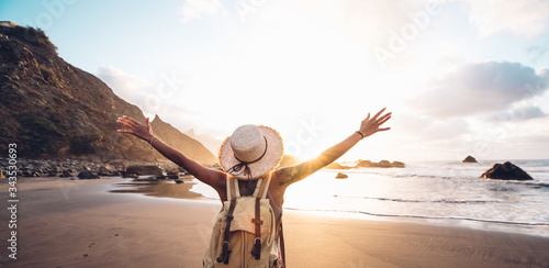 Fotografie, Tablou Happy woman with arms up enjoy freedom at the beach at sunset