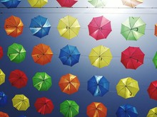 Directly Below Shot Of Colorful Umbrellas Hanging Against Clear Blue Sky