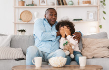 Scary Movie Night. Senior African American Man With His Little Granddaughter Closing Face In Horror At Home