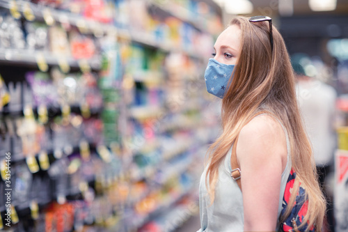 A young woman in a department grocery store wearing a face mask Fototapeta