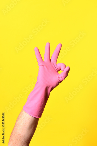 Fényképezés hand with glove and ok sign on yellow background