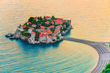 Sveti Stefan Small Island With Red-tiled Roofs, Green Trees And Beautiful Sandy Beach With Sunbeds On The Adriatic Coast Of Montenegro, Budva Municipality. Aerial View At Amazing Sunset Time.