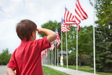 Rear View Of Boy Saluting American Flag Against Sky