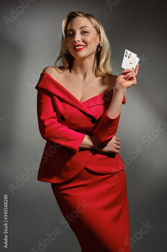 Fototapeta Blonde girl in red dress and black earrings. She smiling, showing two playing cards, posing on gray studio background. Poker, casino. Close-up obraz na płótnie