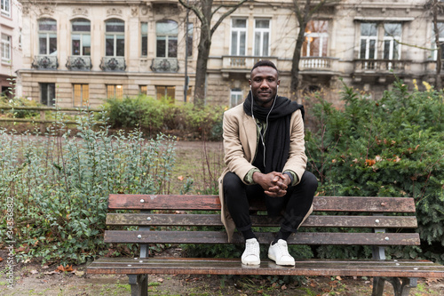 Photo Young Black Man Sitting on Backrest of Park Bench Looking at Camera