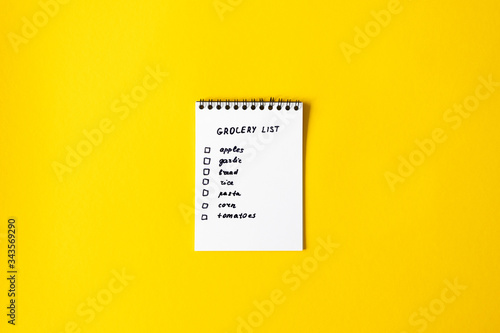 Fototapeta Grocery list paper notepad on yellow background with copy space, top view obraz
