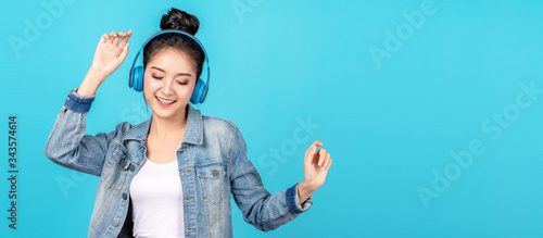 Young happy attractive asian woman using headphone enjoy listen to song in concept of next normal life, pastime or hobby online Canvas Print