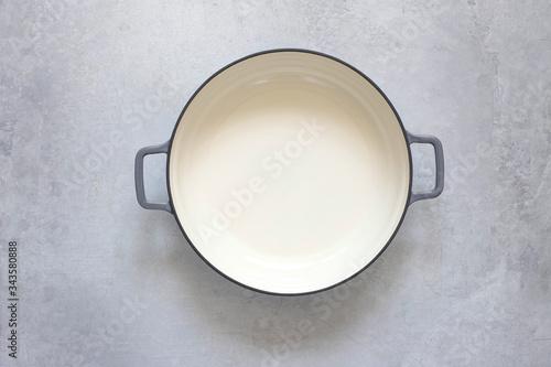 Fototapeta An empty cast-iron pot on a gray concrete background. obraz