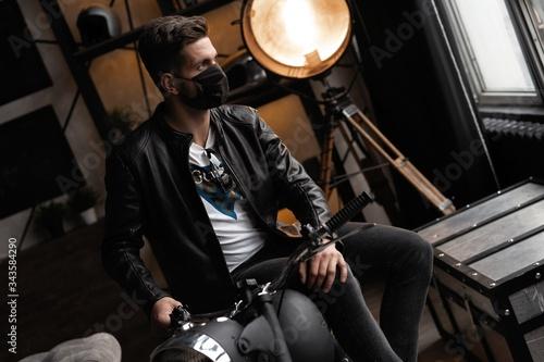 Handsome brutal male biker in black mask in leather jacket sitting on motorcycle looking forward Tablou Canvas