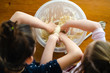 Sisters preparing dough for bread or cake with their hands in a plastic bowl